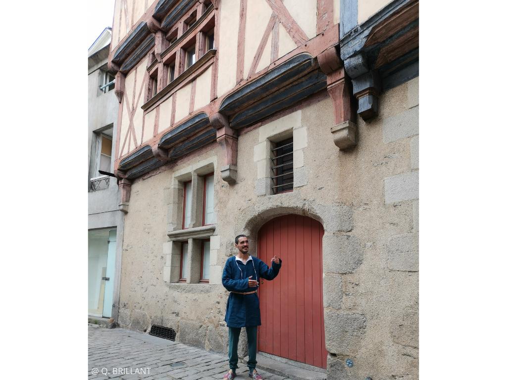 visite insolite guidée par un aubergiste Angers au Moyen Âge devant maison à pan de bois